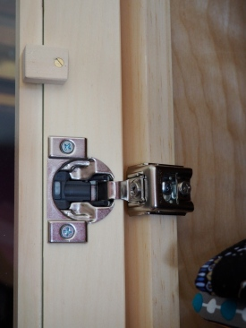 Simple, robust, adjustable -- Euro hinges. Also, simple wooden buttons to hold the door glass in place.