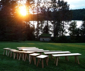 A flock of benches and stools congregates near the shore of a stunning Adirondack lake at sunset